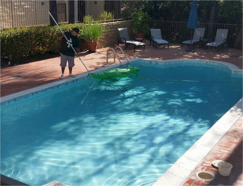 Polished Pools crewman vacuuming debris