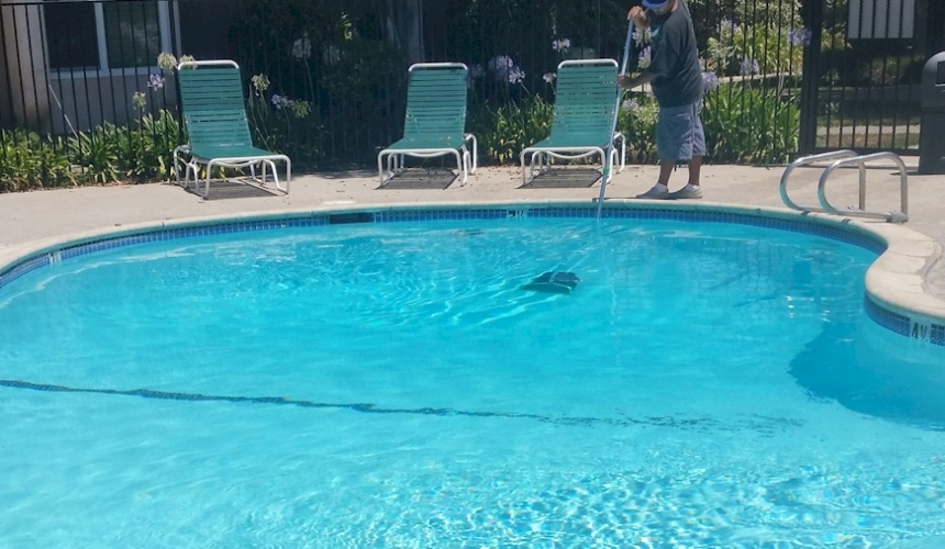 Polished Pools crewman-removing-debrs from HOA pool