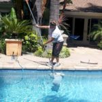 Polished Pools crew member using an underwater battery powered vacuum. Eliminating the pool filtration system.